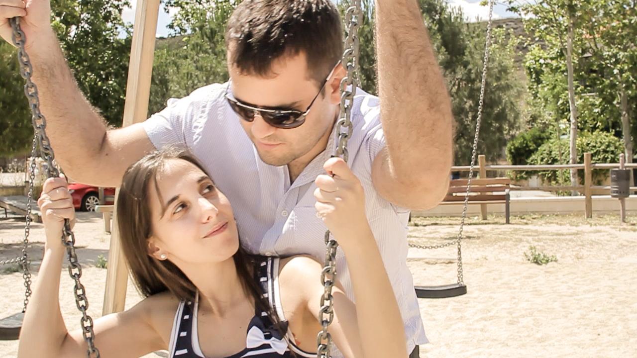 novios besandose en los columpios