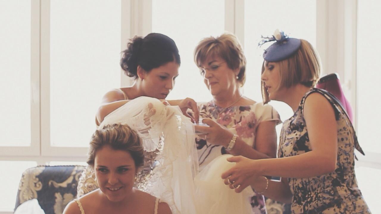 Novia y familia ayudando a vestirse
